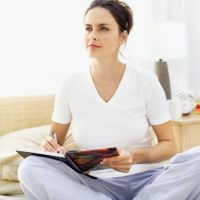 woman sitting with her legs crossed on bed and writing in a journal